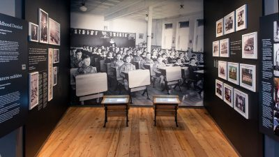 An old image of Indigenous children sitting in school desks at an Indian residential school.